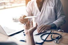 Manlig doktor som räcker ett recept till patienten Fotografering för Bildbyråer