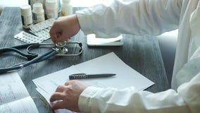 Manlig doktor som skriver pannan för medicinsk historia stock video