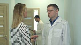Manlig doktor som talar till patienten för ung kvinna i sjukhuskorridoren arkivfilmer