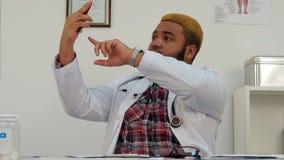 Manlig doktor som tar roliga selfies och visar upp tummen arkivfilmer