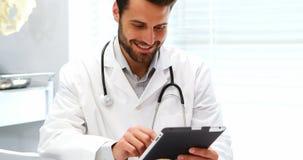 Manlig doktor Using Digital Tablet lager videofilmer