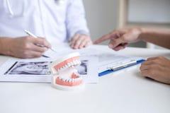 Manlig doktors- eller tandl?karehandstilrapport som arbetar med modellen f?r tandr?ntgenstr?lefilm, och utrustning som anv?nds i  arkivbilder