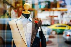 Manlig dräkt på en träskyltdocka i shoppafönstret Begreppsmode, design, Arkivfoton