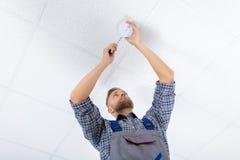 Manlig elektriker Fixing Smoke Detector royaltyfria foton