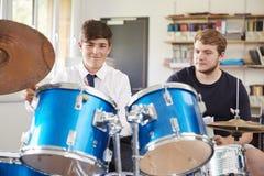 Manlig elev med kurs för lärarePlaying Drums In musik arkivbild