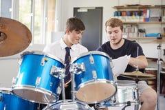 Manlig elev med kurs för lärarePlaying Drums In musik royaltyfri foto