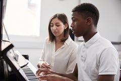 Manlig elev med kurs för lärarePlaying Piano In musik arkivbilder