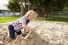 Manlig elev på den Montessori skolan som spelar i sand Pit At Breaktime royaltyfria bilder