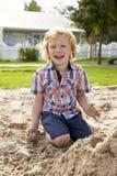 Manlig elev på den Montessori skolan som spelar i sand Pit At Breaktime arkivfoto