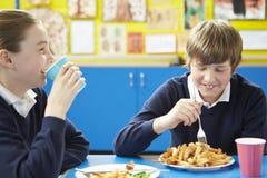 Manlig elev som äter sjuklig skolalunch royaltyfri foto