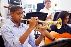 Manlig elev som spelar trumpeten i högstadiumorkester arkivbild