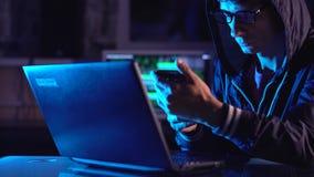 Manlig en hacker i huven som rymmer telefonen i h?nder som f?rs?ker att hacka mobil enhetmolnet i m?rkret under neonljus stock video