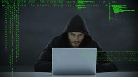 Manlig en hacker som använder en bärbar dator arkivfilmer