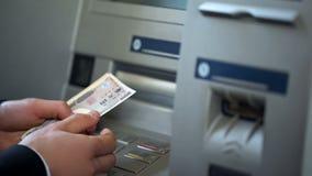 Manlig fående japansk yen från maskinen för automatisk kassör, återta för kassa royaltyfria bilder