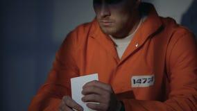 Manlig fånge i handbojor som ser fotoet som känner sig bedrövlig saknad älskling lager videofilmer