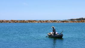 Manlig fisher i fartyget som ut tar ankaret från havsvatten arkivfilmer