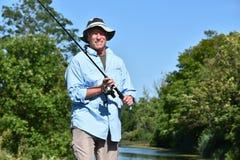 Manlig fiskare Smiling With Fishing Rod Outdoors för gammal pensionär royaltyfri bild