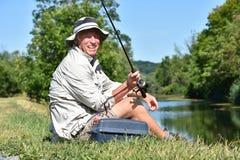 Manlig fiskare Smiling With Fishing Rod Outdoors för pensionär royaltyfri fotografi