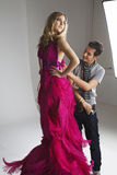 Manlig formgivare som justerar klänningen på modemodell i studio Arkivbilder