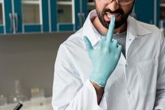 Manlig forskare i det vita laget som tar bort den skyddande handsken förbi tänder i labb Arkivbild