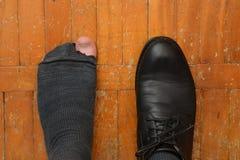 Manlig fot i en sko och sönderriven socka Fotografering för Bildbyråer