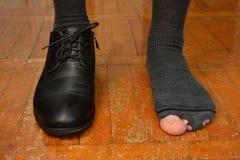 Manlig fot i en sko och sönderrivna sockor på vit bakgrund Arkivbild
