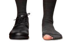 Manlig fot i en sko och sönderrivna sockor som isoleras på vit bakgrund Royaltyfri Bild