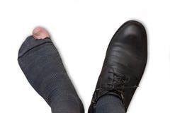 Manlig fot i en sko och sönderrivna sockor som isoleras på vit bakgrund Arkivbild