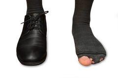 Manlig fot i en sko och sönderrivna sockor som isoleras på vit bakgrund Arkivbilder