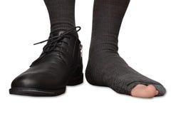 Manlig fot i en sko och sönderrivna sockor som isoleras på vit bakgrund Royaltyfria Bilder