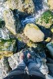Manlig fot i gymnastikskor på stranden med stora stenar Fotografering för Bildbyråer