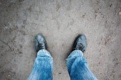 Manlig fot i jeans och svartskor på den lantliga vägen Arkivbilder