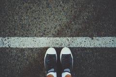 Manlig fot nära den vita linjen på asfalt royaltyfri bild