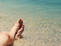 Manlig fot på en strand mot havet i en solig dag för sommar arkivbilder