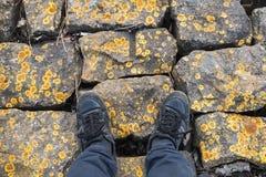 Manlig fot ställning på grova stenar Arkivbild