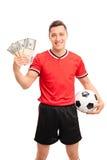 Manlig fotbollsspelare som rymmer några buntar av pengar Royaltyfria Foton