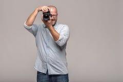Manlig fotograf som fokuserar en bild Arkivbild