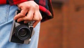 Manlig fotograf som rymmer en gammal kamera i händer Royaltyfri Bild