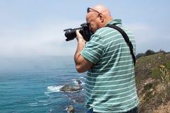 Manlig fotograf som tar bilder på klippan royaltyfria foton