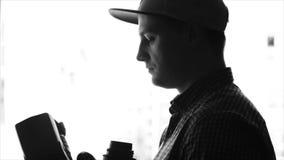 Manlig fotografinnehavkamera och lins stock video