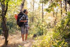 Manlig fotvandrare som går i skogen Arkivbild