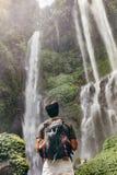 Manlig fotvandrare som ser vattenfallet Fotografering för Bildbyråer