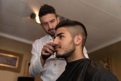 Manlig frisör Cutting Hair Of som ler manklienten Arkivfoton
