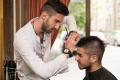 Manlig frisör Cutting Hair Of som ler manklienten Arkivbild