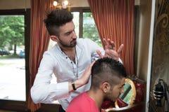 Manlig frisör Preparing Hair Of som ler manklienten Arkivfoton