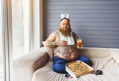 Manlig frossare som äter skräpmat med alkohol royaltyfria foton