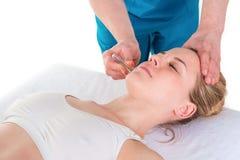 Manlig fysioterapeut som ger den head massagen med ett sugorganhjälpmedel till a arkivbild