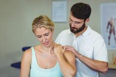 Manlig fysioterapeut som ger halsmassage till den kvinnliga patienten arkivbilder