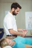 Manlig fysioterapeut som ger handmassage till den kvinnliga patienten arkivbild