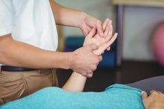 Manlig fysioterapeut som ger handmassage till den kvinnliga patienten royaltyfria bilder